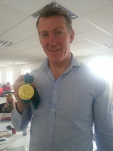 Champion rower, Ben Hunt-Davis MBE holding his Olympic gold from Sydney